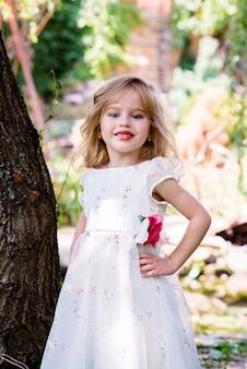 Kleines mädchenkind mit langen blonden haaren und hübschem lächelndem glücklichem gesicht im weißen kleid der abschlussballprinzessin, das im garten mit grünem gras sonnigen tag im freien steht