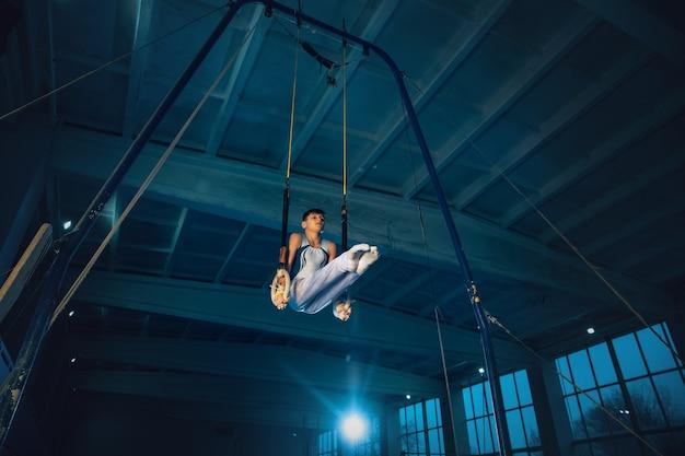 Kleines männliches turnertraining im fitnessstudio, flexibel und aktiv. kaukasischer fitter junge, athlet in weißer sportbekleidung, der in übungen für das gleichgewicht auf den ringen übt. bewegung, aktion, bewegung, dynamisches konzept.