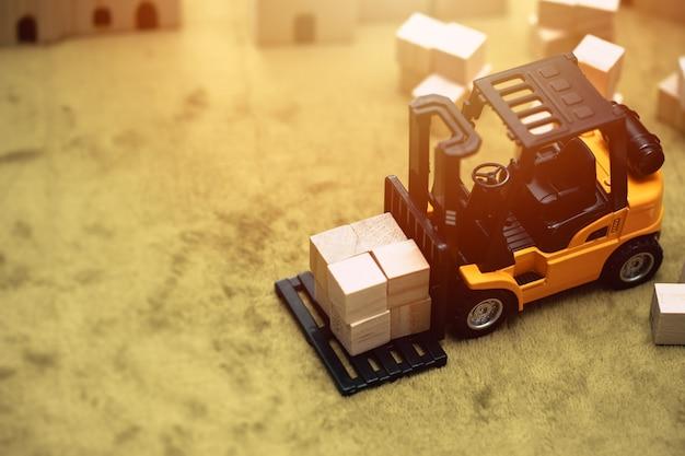 Kleines modell eines gabelstaplerautos, das bewegliche güter für den transport, versand und das hintergrundkonzept der lagerwirtschaft arbeitet