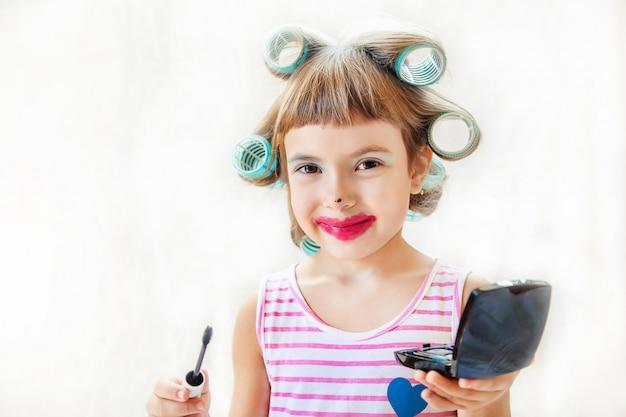 Kleines modemädchen. mädchen macht ihr make-up und maniküre. selektiver fokus.