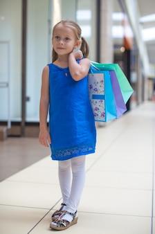 Kleines modemädchen mit paketen im großen einkaufszentrum
