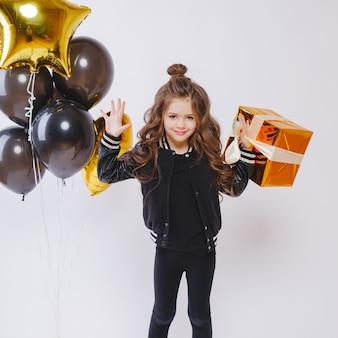 Kleines modernes hipster-mädchen in modekleidung steht in der nähe von luftballons und hält goldgeschenk. geburtstag.