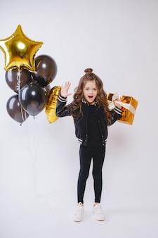 Kleines modernes hipster-mädchen in modekleidung steht in der nähe von luftballons und hält goldgeschenk. pose gesicht. geburtstag.