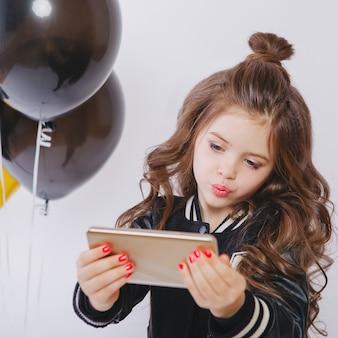 Kleines modernes hipster-mädchen in modekleidung und luftballons, selfie, kuss. machen sie ein foto am telefon