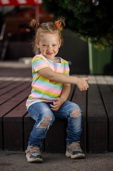 Kleines modisches mädchen in jeans und einem farbigen t-shirt