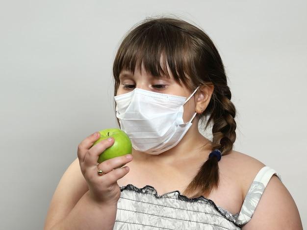 Kleines molliges mädchen in der medizinischen gesichtsmaske hält grünen apfel