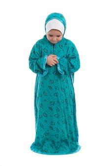 Kleines muslimisches mädchen, das in einem traditionellen kostüm betet