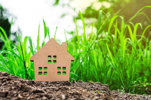 Kleines musterhaus in der grünen rasenfläche. - familie, immobilien oder darlehen für geschäftsinvestitionskonzept.