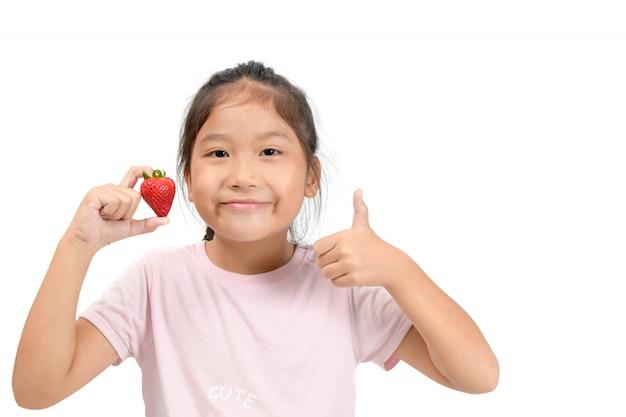 Kleines nettes asiatisches mädchen, das eine erdbeere hält und sich daumen zeigt,