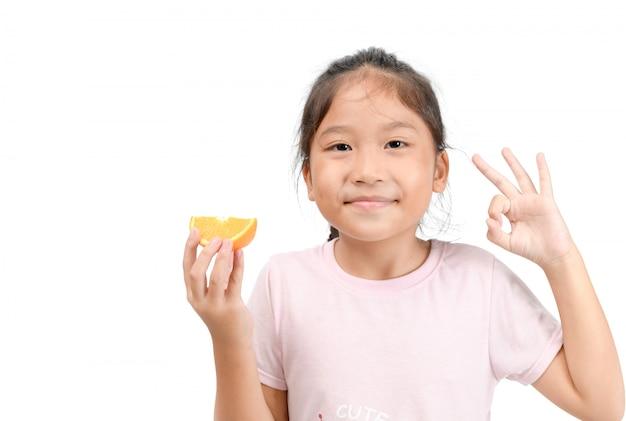 Kleines nettes asiatisches mädchenlächeln und halten einer geschnittenen orange