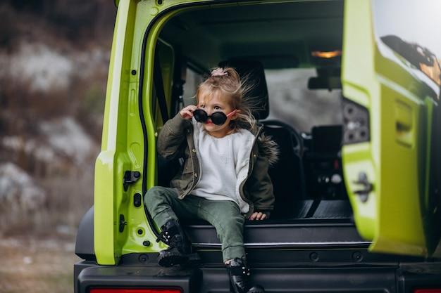 Kleines nettes baby, das auf der rückseite des autos sitzt