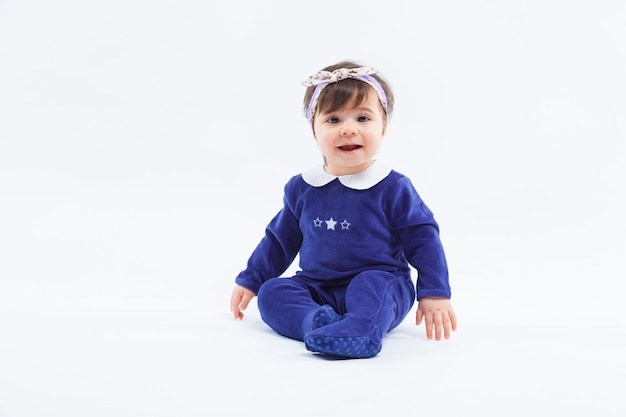 Kleines nettes entzückendes lächelndes mädchen mit bogen im haar, das im studio aufwirft auf weiß sitzt