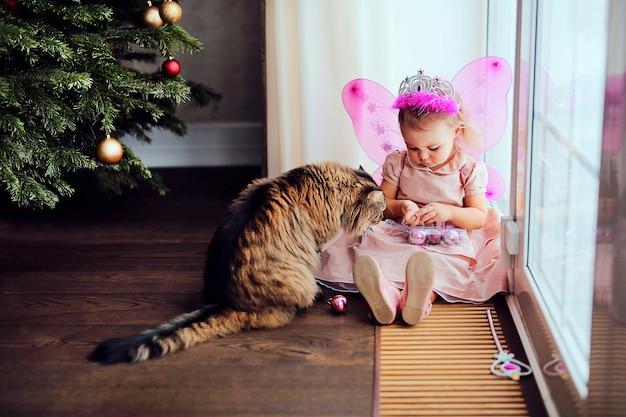 Kleines nettes kind im feenhaften kostüm, das mit katze nahe weihnachtsbaum spielt