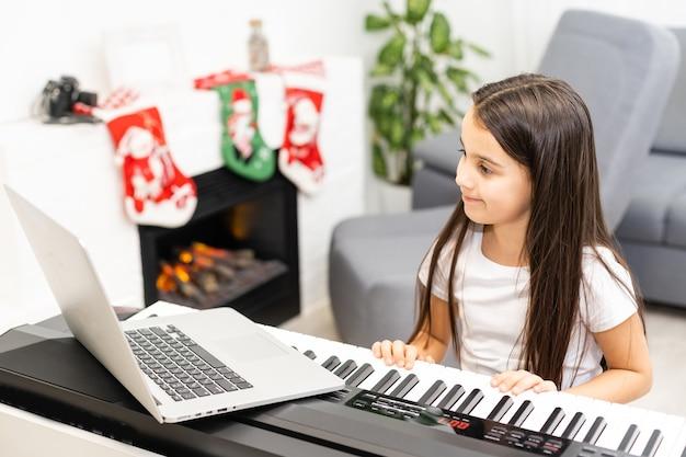 Kleines nettes kindermädchen, das das klavier mit verziertem weihnachten auf dem hintergrund spielt. weihnachtsfeier während der pandemie