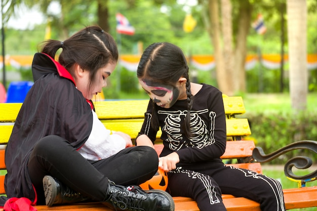 Kleines nettes mädchen asien in halloween-kostüm teilt bonbons und süßigkeiten beim sitzen an der bank auf dem spielplatz.