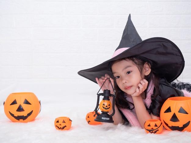 Kleines nettes mädchen cosplay als hexe und halten der kürbislampe und -eimer auf weißem hintergrund.