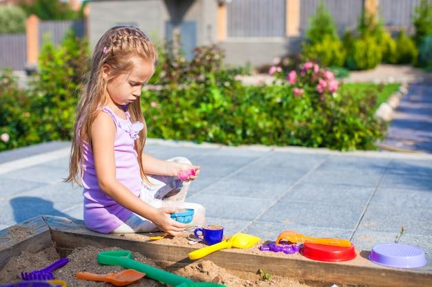 Kleines nettes mädchen, das am sandkasten mit spielwaren im yard spielt