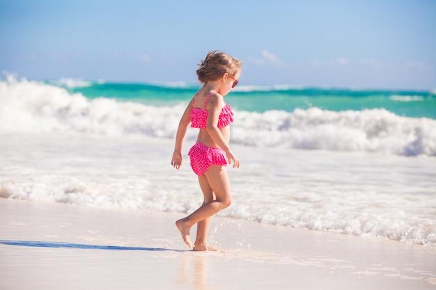 Kleines nettes mädchen, das auf den weißen sandigen strand in mexiko geht