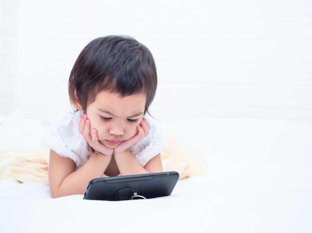 Kleines nettes mädchen, das auf weißem boden liegt und smartphone mit ernsthaft aufpasst.