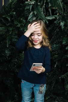 Kleines nettes mädchen, das das intelligente telefon setzt hand auf ihren kopf betrachtet