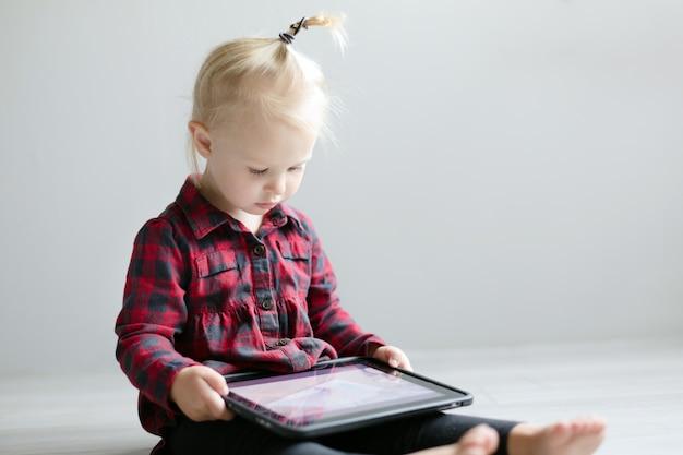Kleines nettes mädchen, das eine karikatur auf der tablette aufpasst