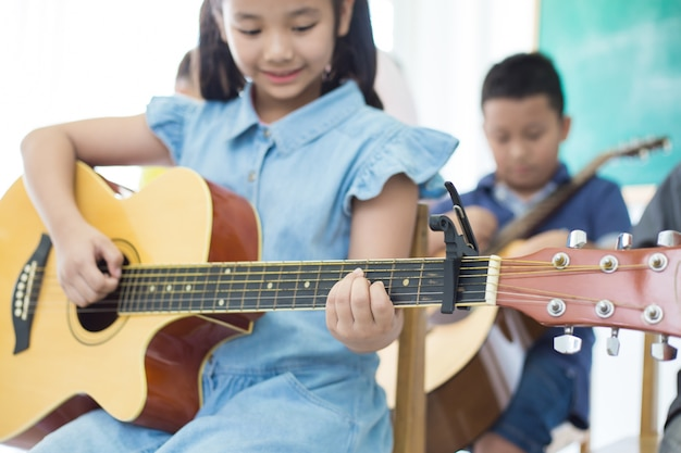 Kleines nettes mädchen, das gitarre spielt und im musikklassenzimmer lächelt.