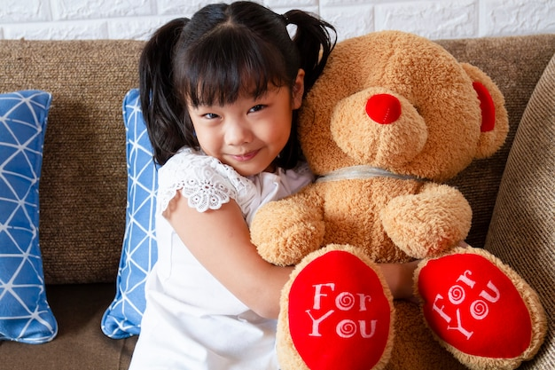 Kleines nettes mädchen, das großen teddybären mit glück zeigt