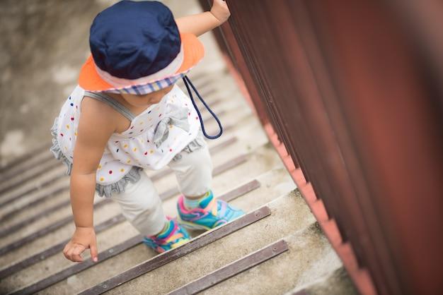Kleines nettes mädchen, das herauf die treppe geht. kind erste schritt konzept.