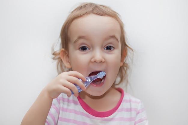 Kleines nettes mädchen, das ihre zähne smailing und putzt.
