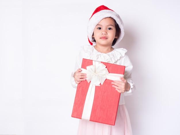 Kleines nettes mädchen, das santa claus-kappe trägt und rote geschenkbox hält