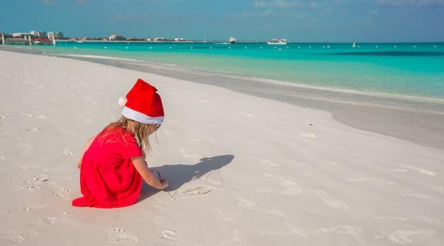 Kleines nettes mädchen in roter weihnachtsmütze, die auf dem strand spielt