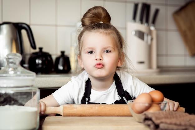 Kleines nettes mädchen kocht auf küche. spaß beim backen von kuchen und keksen haben