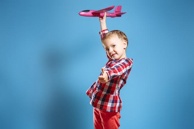 Kleines nettes mädchen mit einem spielzeugflugzeug, das sich ihren daumen zeigt.
