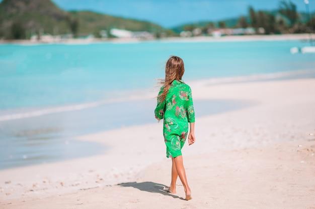 Kleines nettes mädchen mit muschel in den händen am tropischen strand.