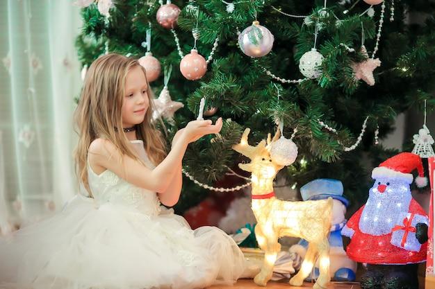 Kleines nettes mädchen nahe weihnachtsbaum. kinder unter weihnachtsbaum mit geschenkboxen.