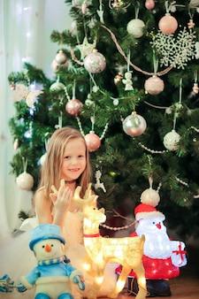 Kleines nettes mädchen nahe weihnachtsbaum.