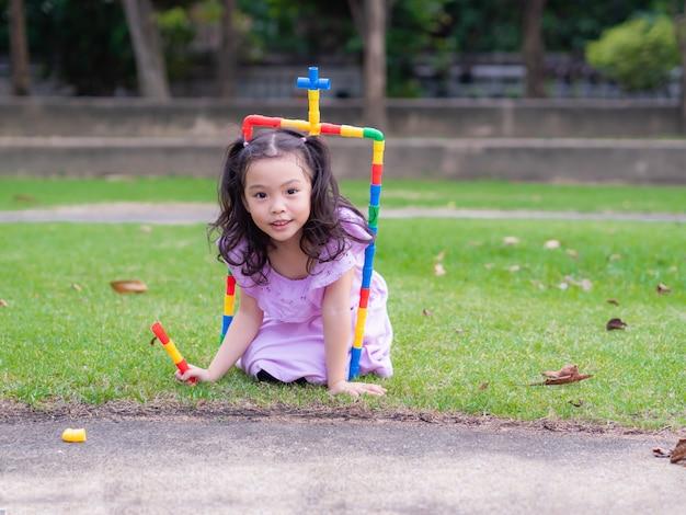 Kleines nettes mädchen spielen das rohrspielzeug, angeschlossen an das tor und den eingang.