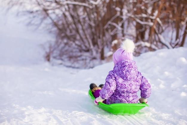 Kleines nettes mädchen zieht einen schlitten am warmen wintertag