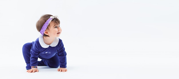 Kleines nettes neugieriges entzückendes lächelndes mädchen mit bogen im kriechenden sitzen des haares im studio, das auf weißem hintergrund aufwirft