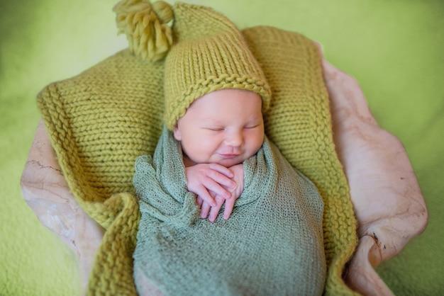 Kleines neugeborenes baby in gestrickter kleidung schläft auf dem kissen