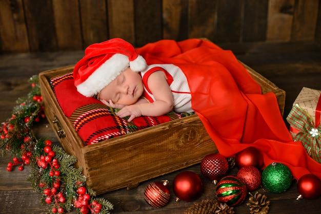 Kleines neugeborenes mädchen acht tage alt im weihnachtsanzug