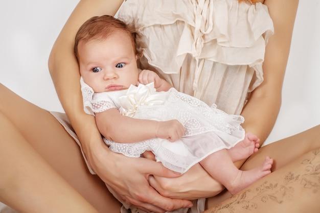 Kleines neugeborenes mädchen, das in den armen der mutter liegt.