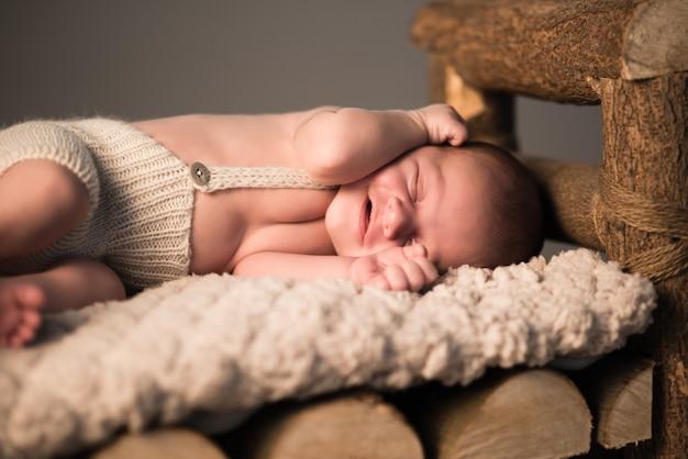 Kleines neugeborenes schlafendes baby liegt auf der haut auf einem hölzernen hocker auf einem grauen hintergrund