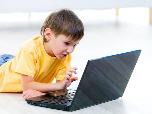 Kleines neugieriges kind mit laptop auf dem boden - drinnen