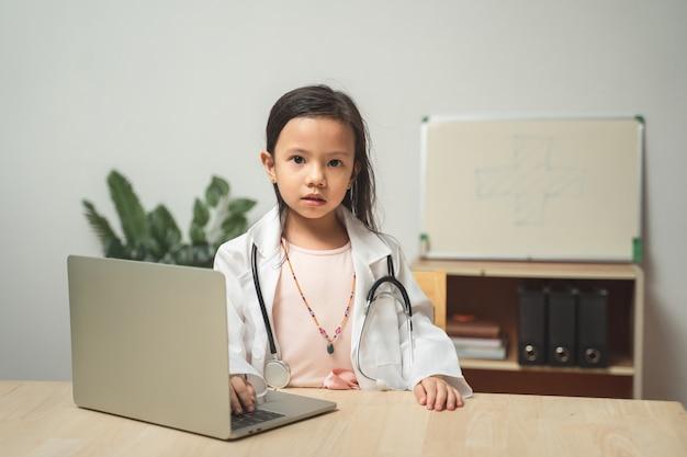 Kleines niedliches asiatisches kindermädchen, das doktor spielt, der weiße unifornische und stethoskop betrachten kamera in gemütlichem wohnzimmer zu hause betrachtet