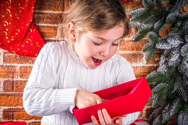 Kleines niedliches kaukasisches blondes mädchen öffnet weihnachtsgeschenkboxen.