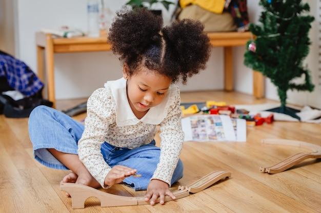 Kleines niedliches kindermädchen genießen das spielen des holzpuzzles auf dem holzboden zu hause im wohnzimmer.