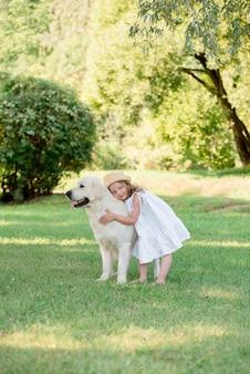 Kleines niedliches kleinkindmädchen, das mit ihrem großen weißen schäferhund spielt.