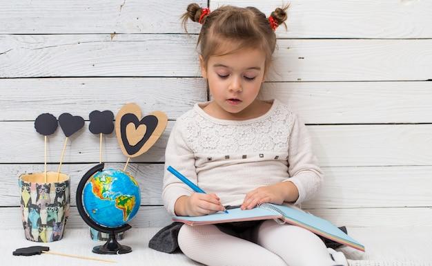 Kleines niedliches mädchen schulmädchen sitzt auf einem weißen hölzernen hintergrund mit einem globus in seinen händen und einem notizbuch, das konzept des wissens