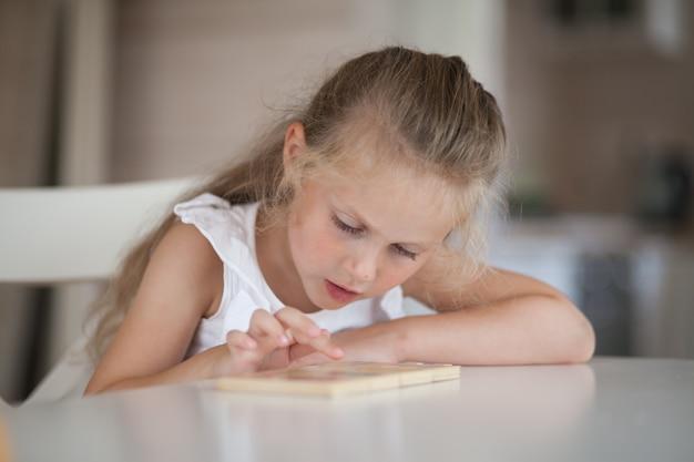 Kleines niedliches vorschulkindkind, das lernspiele mit holz spielt